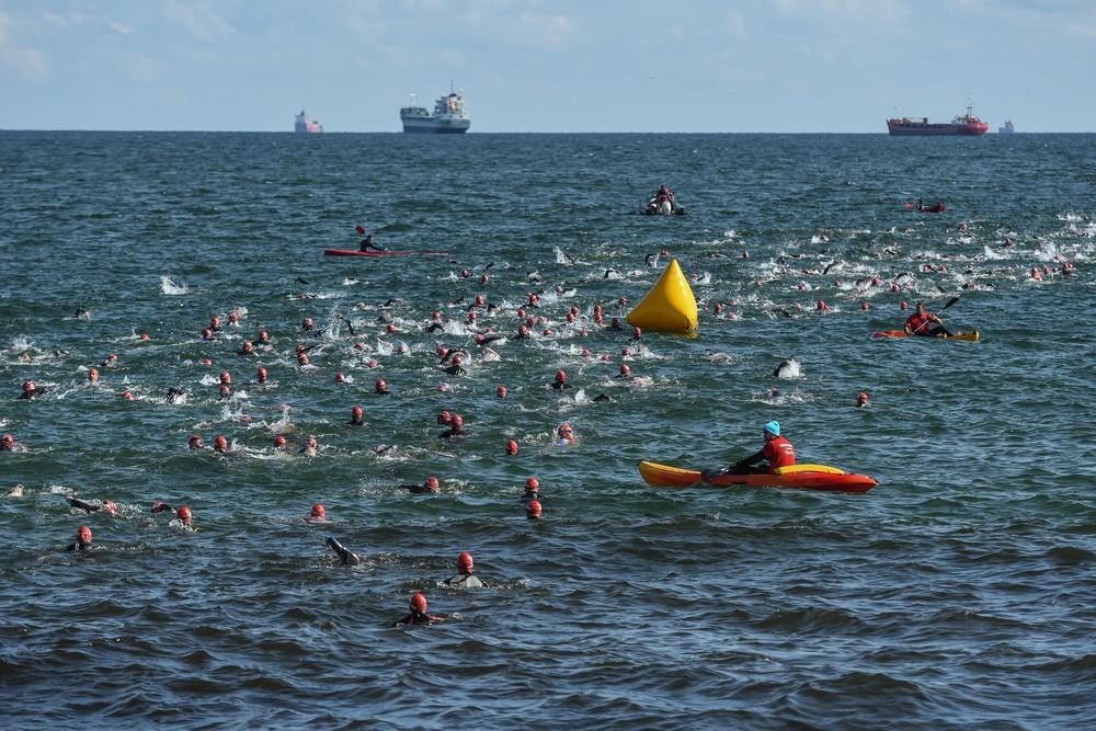 Płynący zawodnicy wZatoce Gdanskiej, obok ratownik arekurujący na kajaku, wtle trzy statki
